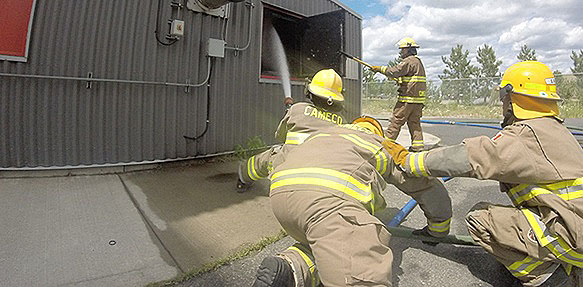 Firefighters training to put out a fire.