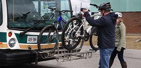 Male cyclist lifting one of two bicycles onto the rack on the front of a transit bus.