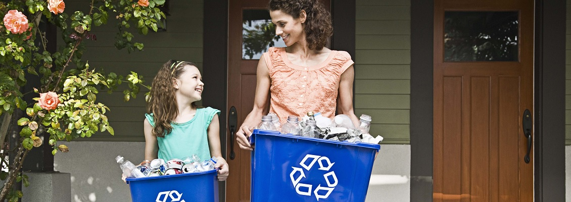 A woman and child holding blue recycling bins filled with plastic bottles and cans.