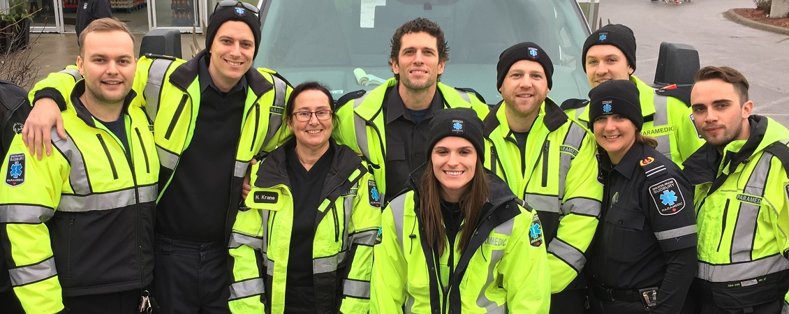 Six male paramedics and three female paramedics in their uniforms smiling.