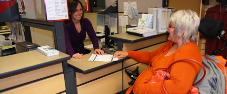 A woman using a wheelchair speaks with a smiling customer service representative.